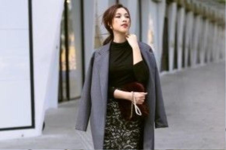 Á hậu phối áo khoác dáng dài, áo cổ lọ cùng chân váy ren họa tiết hoa 3D sang trọng tạo nên một set đồ monochrome thời thượng. Chiếc túi xách lông màu đỏ cũng là một phụ kiện yêu thích của nhiều tín đồ thời trang trong năm vừa qua.
