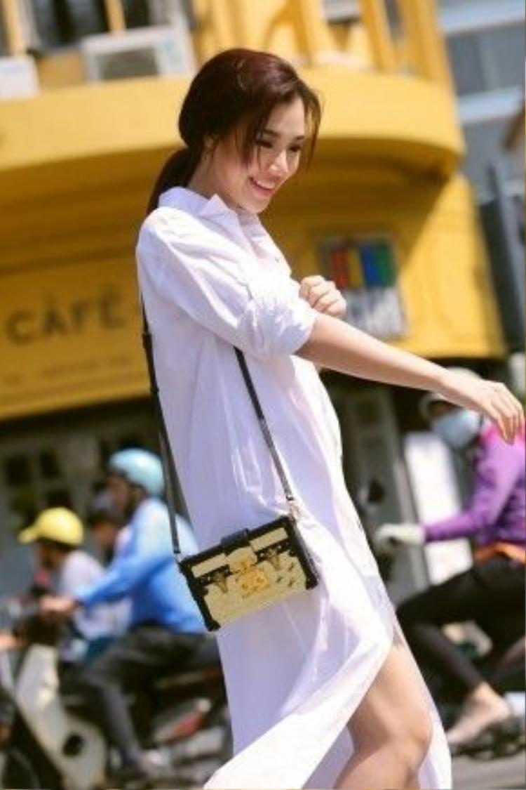 Cô chọn những đôi giày cao gót mũi nhọn cổ điển và mẫu túi xách nhỏ đính kim loại để hoàn thiện vẻ tinh tế cho bộ trang phục.