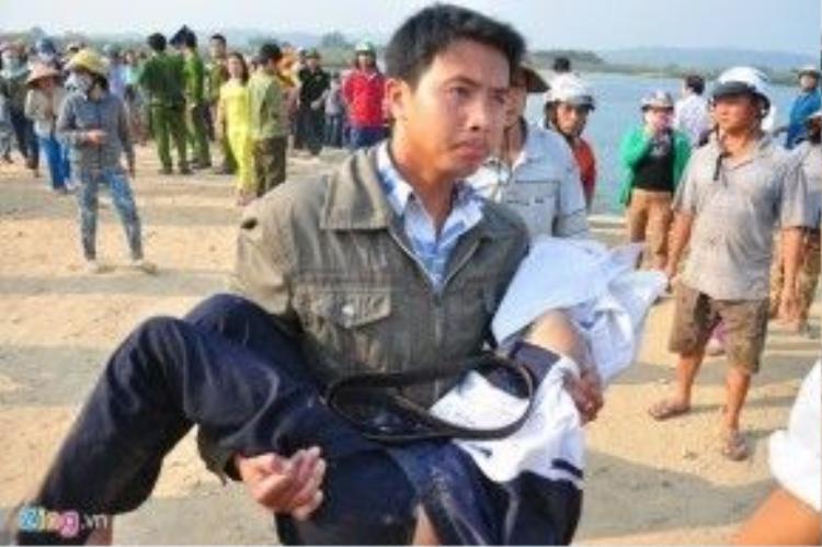 Một người đưa thi thể học sinh lên bờ.