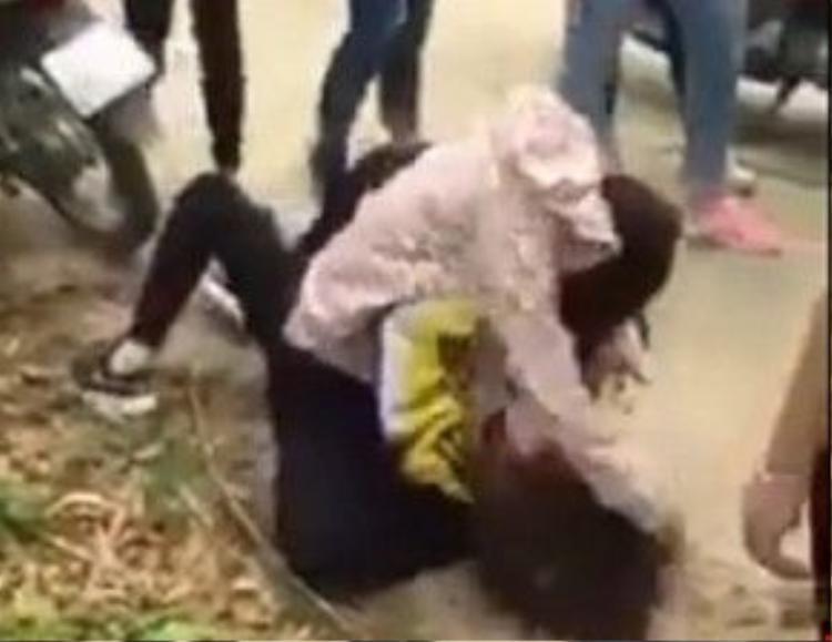 Nữ sinh mặc đồng phục liên tiếp bị túm tóc và đập đầu xuống đường. Ảnh cắt từ clip.