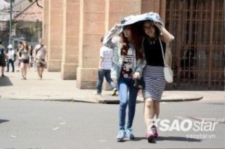 2 cô gái dùm áo trùm đầu trước cổng nhà thờ Đức Bà, quận 1.