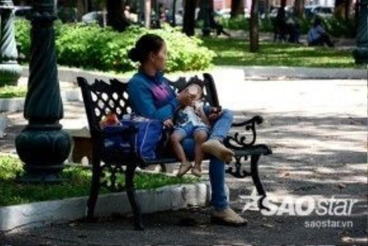 Thời tiết nắng nóng nên nhiều người tìm đến khu vực có bóng cây, công viên để nghỉ mát. Trong ảnh một người phụ nữ ôm con hóng mát ở công viên 23/9, quận 1.