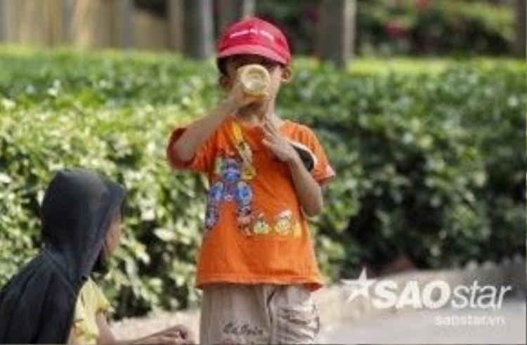 Một cậu bé uống vội ca nước giữa cái nắng gay gắt giữa trưa của Sài Gòn.