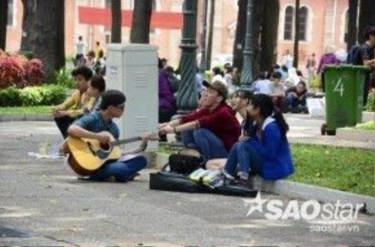 Một nhóm bạn trẻ tụ tập tại công viên 30/4 quận 1 để hóng mát và ca hát.