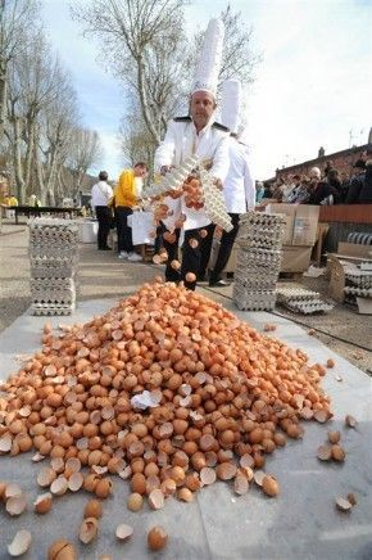 Một đầu bếp Giant Omelette Brotherhood of Bessières đổ vỏ trứng chất đống. Hơn 15,000 quả trứng được sử dụng để tạo nên món ăn đầy ý nghĩa này.