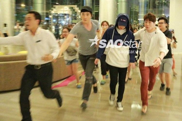 Ảnh cận cảnh: Quản lý gần như ôm trọn Xiumin (EXO) để tránh cơn bão fan Hà Nội