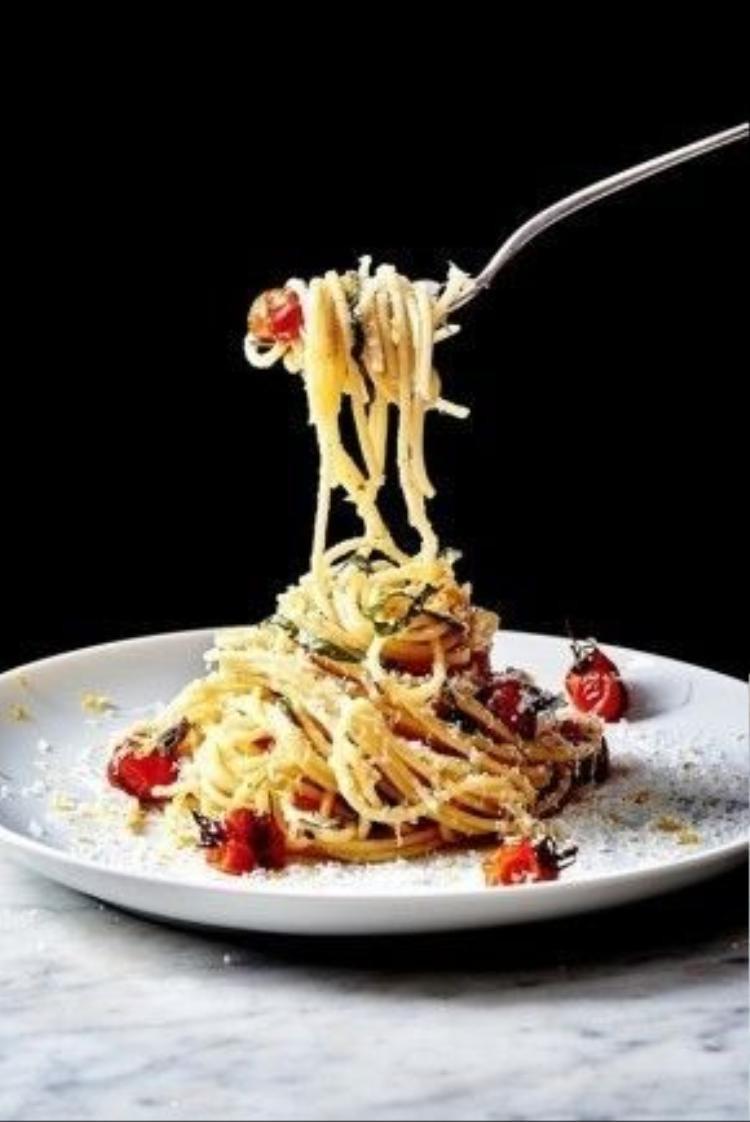 """Bạn sẽ chỉ mất khoảng 30 phút để thực hiện món spaghetti này. Công đoạn """"phức tạp"""" nhất là rán cà chua bi cho nứt vỏ bên ngoài. Mì Ý sau khi nấu chín được trộn với bơ và nước cốt chanh. Khi ăn, rắc thêm phô mai và húng quế."""