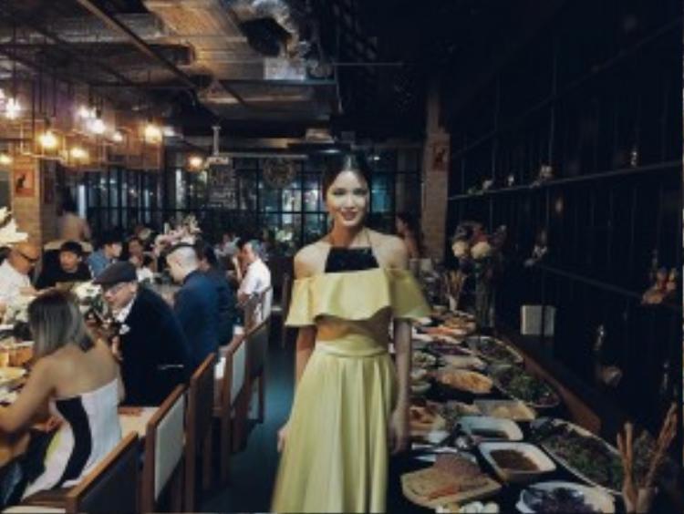 Chà Mi next top khoe ảnh đi ăn tối trong trang phục nền nã được lấy hứng cảm từ chiếc áo trễ vai và áo yếm của NTK Hoàng Minh Hà.