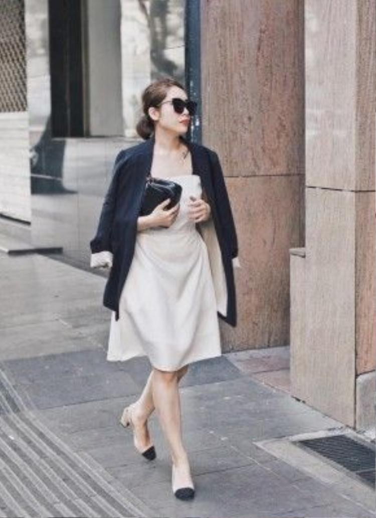 """Fashionista Lâm Thúy Nhàn đồng thời là chủ thương hiệu của store thời trang nổi tiếng xuất hiện trên phố lần này với style cổ điển của những năm 50s. Mốt đầm xòe gam trắng tinh tế, áo khoác choàng đen hờ hững qua vai, đi kèm là đôi giày two-tone đến từ thương hiệu trứ danh Chanel đồng điệu với cả set đồ. Cặp kính ngoại cỡ wayfarer """"chất lừ"""" chính là điểm mấu chốt tạo nên phong cách cô nàng."""