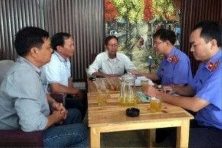 Đại diện VKSND huyện Bình Chánh đang chuẩn bị thủ tục trao quyết định đình chỉ vụ án, đình chỉ bị can với ông Tấn tại quán Xin Chào.