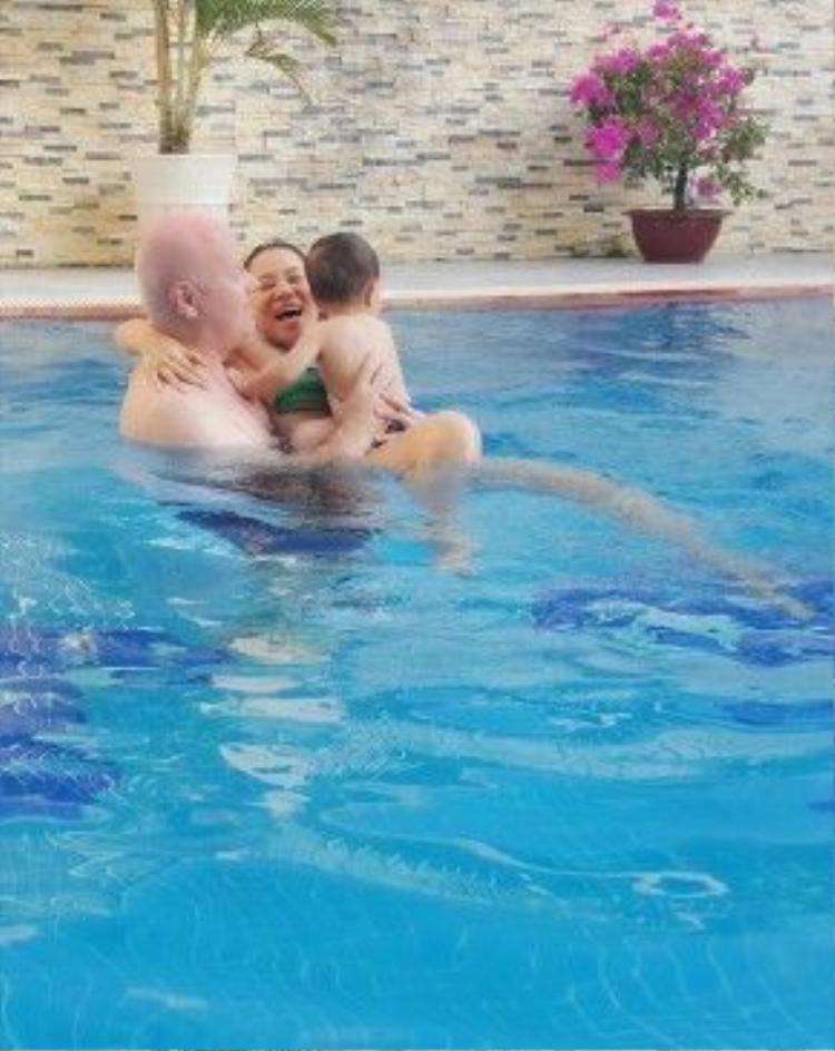 Nữ ca sĩ cười sung sướng khi được ông xã bế hai mẹ con xuống bể bơi.