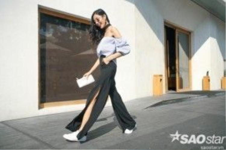 Chân dài diện áo chemise trễ vai, quần ống loe xẻ hông khoe chân dài tít tắp.