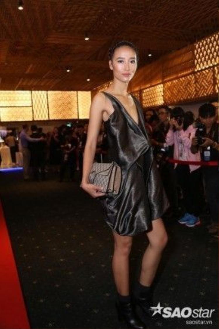 Chân dài Trang Khiếu xuất hiện trên thảm đỏ với thiết kế vải bóng, tạo hiệu ứng thị giác cho người đối diện dưới ánh đèn sân khấu. Cô diện túi hiệu Dionyses GG có giá hơn 2000 USD.