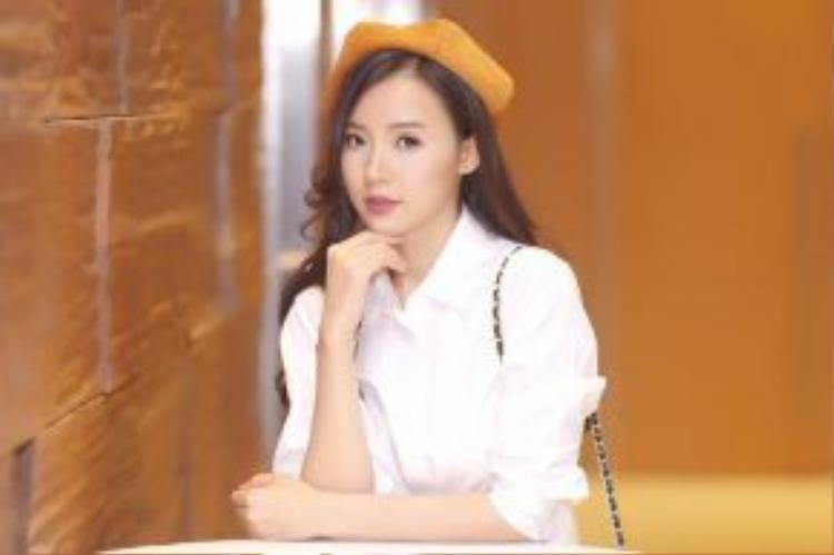 Một chiếc áo trắng hoàn toàn được nhấn nhá bởi chiếc mũ màu vàng khaki.