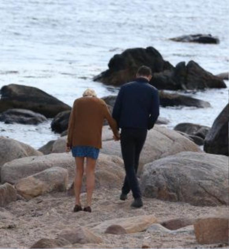 Cả hai mặc trang phục đời thường đơn giản, đeo kính đen. Họ tay trong tay đến mỏm đá nhìn ra trước biển.