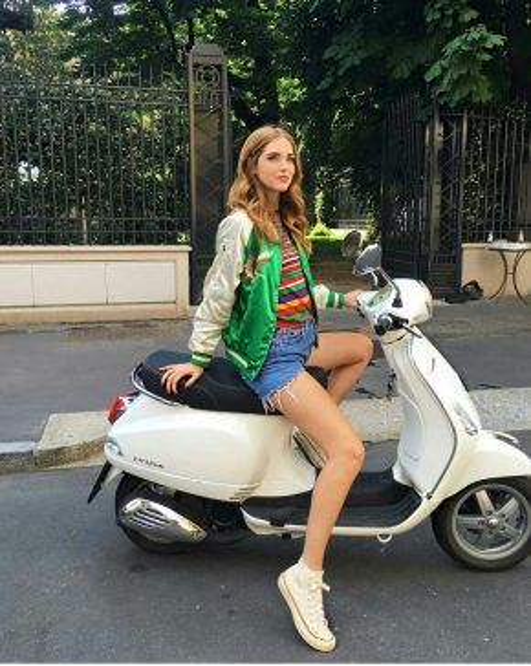 Cô nàng blogger Chiara biến hóa bản thân với set đồ tưởng chừng như khó kết hợp bao gồm áo thun kẻ sọc màu sắc và một chiếc áo khoác bomber họa tiết, hai màu sắc hòa quyện với nhau tạo nút thắt lạ mắt cho tổng thể trang phục cũng như tạo sự năng động cho người mặc bằng một đôi sneaker trắng đơn giản.