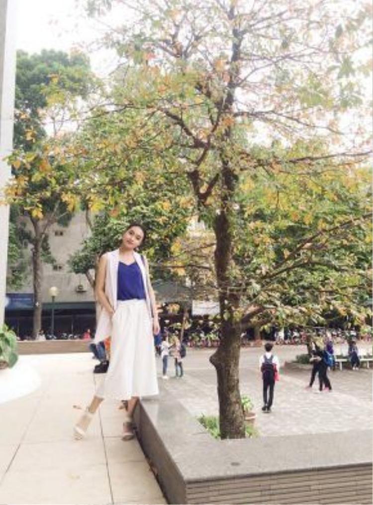 Vũ Lê Ngọc Anh - nàng hoa khôi Đại học Ngoại thương năm 2015 diện cây trắng tới lớp. Chiếc quần culottes và áo gile dáng dài khoác bên ngoài rất kiểu cách chứng tỏ cô nàng là người nắm bắt khá nhanh các xu hướng. Chiếc áo 2 dây màu xanh bên trong là điểm nhấn của cả set đồ.