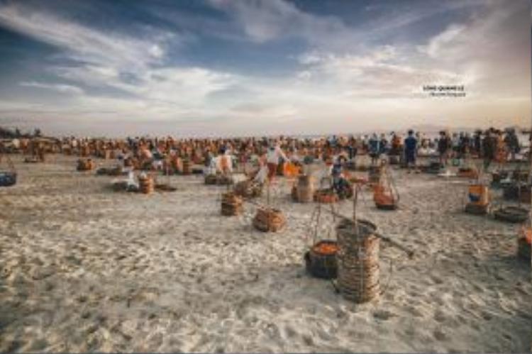 Quang cảnh buổi sáng sớm ở bãi biển, những gánh hàng cá đang đợi tàu ghe về.