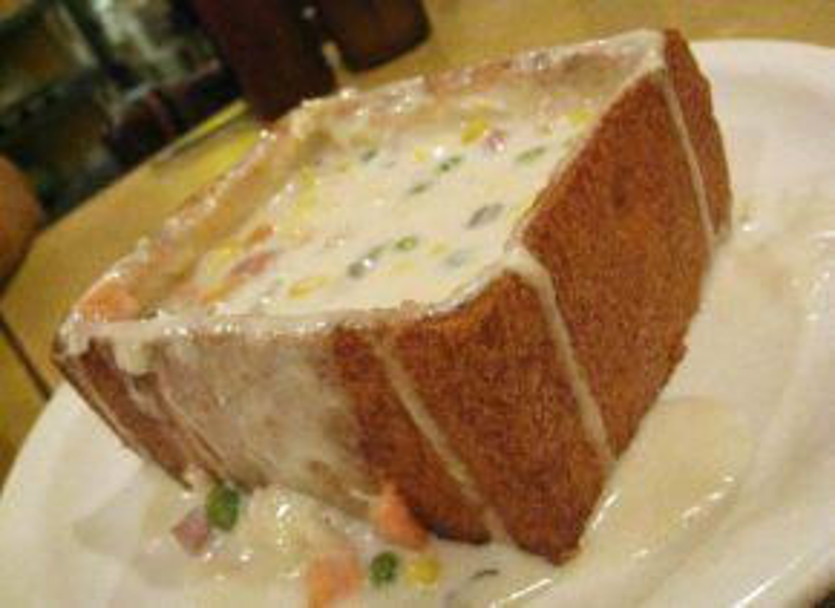Bánh mì quan tài truyền thống thực chất là một lát bánh mì nướng giòn có độ dày khoảng 3-5 cm, được khoét rỗng ở giữa và có nắp đậy phía trên. Nhân bên trong là hỗn hợp của khoai tây, cà rốt thái hạt lựu, đậu xanh, gan lợn, thịt, tôm và một số loại rau hương liệu khác, tạo thành hỗn hợp sánh mịn với hương vị khó cưỡng. Ảnh: Lataco.
