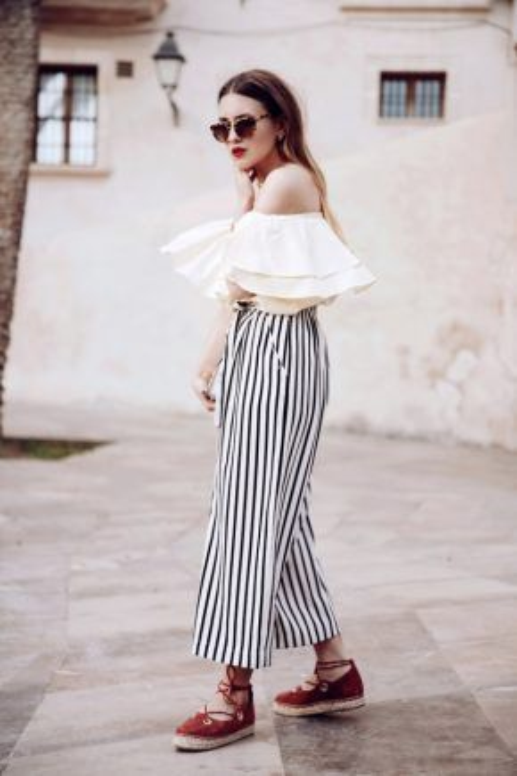 """Khi áo trễ vai và quần jeans đã trở thành công thức """"đại chúng"""" mà ai cũng mặc thì rõ ràng là bạn sẽ nổi bật hơn hẳn khi diện áo trễ vai cùng với quần kẻ sọc như cô nàng này. Và đừng quên chọn giày đế cói để hoàn thiện set đồ của mình."""