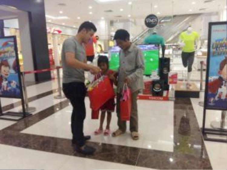 Đại diện siêu thị trao phần quà cho 2 cha con - (Ảnh: Facebook C.K)