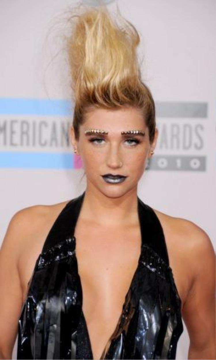 Lấy hình ảnh đúng chất Metallic girl, Kesha sử dụng kiểu gắn đinh tán lên lông mày rất lạ kèm theo đó son môi màu bạc cùng style mà mái tóc vuốt dựng hợp đến khó hiểu.