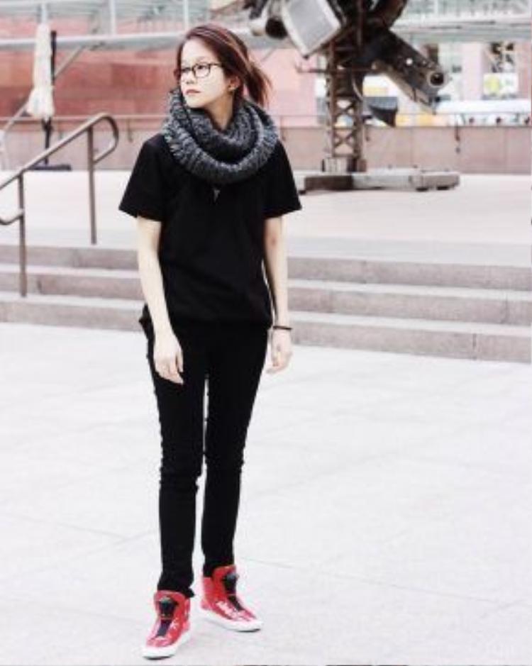 An Nguy đã tạo điểm nhấn bắt mắt cho set đồ đen tuyền của mình bằng một đôi sneaker màu đỏ nổi bật đến từ thương hiệu Versace.