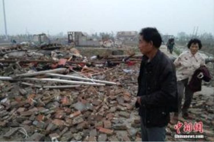 Người dân ở Diên Thành nhìn theo căn nhà đã trở thành đống đổ nát sau thiệt hại kép mưa đá và lốc xoáy chiều nay. Ảnh: Chinanews.