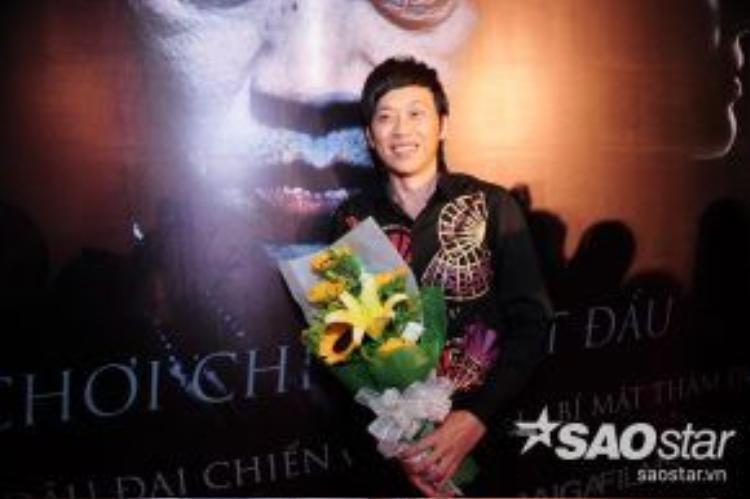 Hoài Linh tạo dáng trước poster phim của chính mình.
