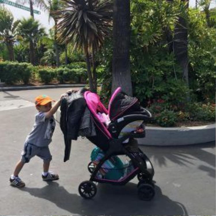 Anh trai Jacky Minh Trí đẩy xe nôi cho em gái.