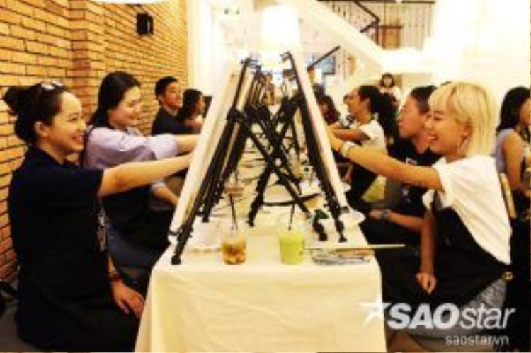 Các học viên đang đặt tay lên toan vẽ để thực hiện nghi lễ.