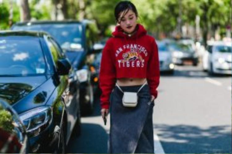"""Hiền Trang kết hợp áo hoodie crop top in họa tiết """"hổ báo"""" cùng chân váy xếp vạt. Cô nàng thêm vào chiếc túi xách ngang eo lạ mắt cùng giày cao gót buộc dây thanh mảnh."""