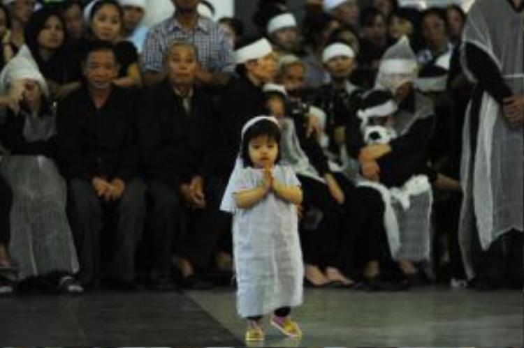 Con gái nhỏ hơn 2 tuổi của trung tá Lê Văn Đình (nhân viên tuần thám trên không) trong lễ tang cha và các đồng đội của cha mình sáng 30/6..(Ảnh: VNE)