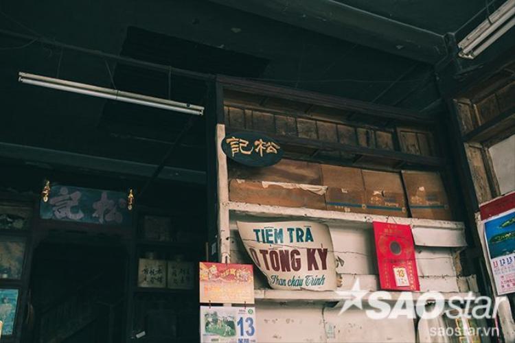 """Những dãy kệ này từng một thời được chất đầy những hộp trà và bánh, nhưng bây giờ chỉ còn lại lớp bụi của thời gian phủ lên. Tấm biển đề hai chữ Hán """"Tòng Ký"""" được cha bà Kha Quyên treo lên vào năm 1913 khi mở tiệm cho đến nay vẫn còn ánh lên nét vàng son thuở nào."""