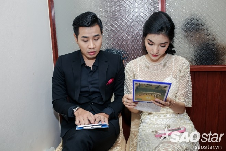 Hai MC chương trình Nguyên Khang và Mỹ Linh chăm chú đọc lại kịch bản trước khi lên sân khấu