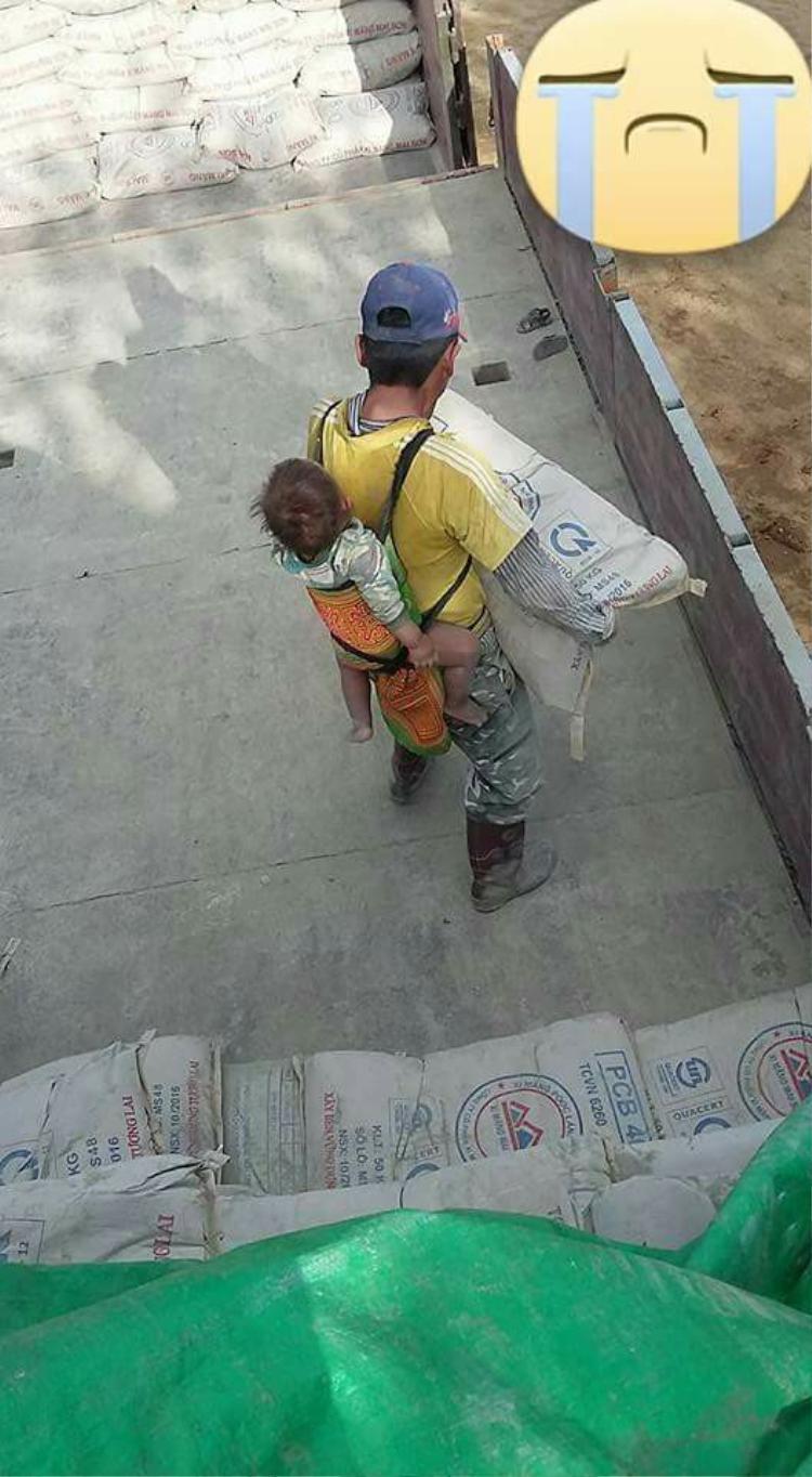 Người bố vừa địu con, vừa vác xi măng kiếm sống. Ảnh V.P.