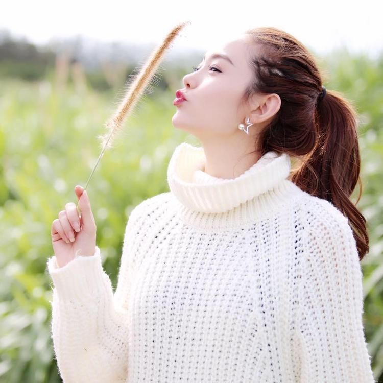 Minh Hằng đẹp ngọt ngào trong chiếc áo len đan màu trắng. Cổ áo được may rộng rãi, mềm mại, bẻ thành nếp gấp.