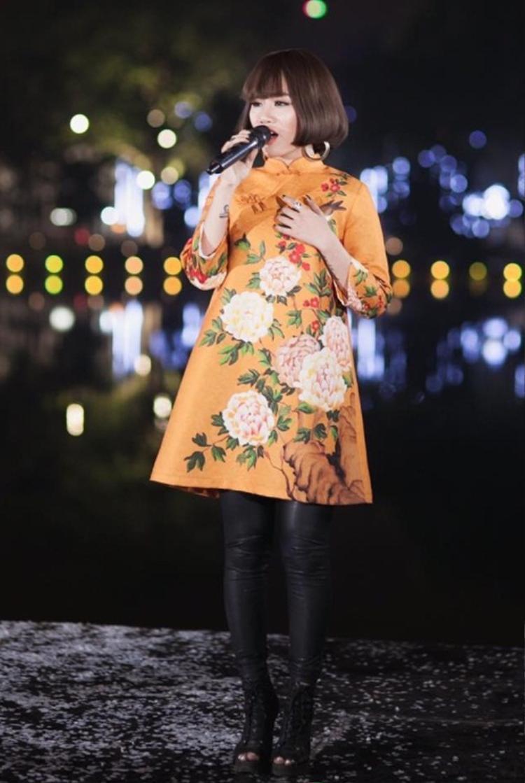 Thiết kế áo dài với phom dáng cách tân về độ ngắn trên đầu gối được mix cùng legging chất liệu da mang đến diện mạo hiện đại, trẻ trung hơn cho giọng ca.