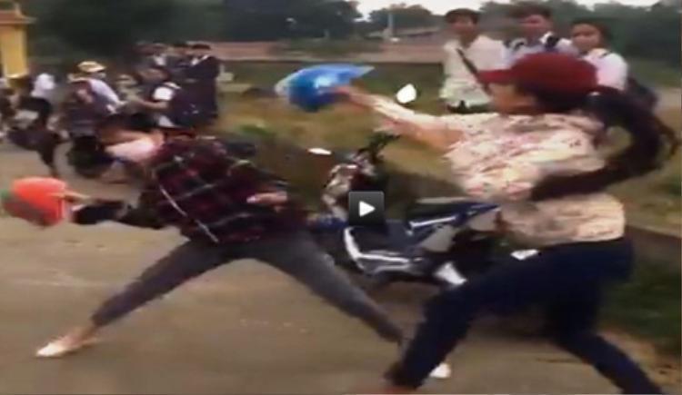 Hai nữ sinh dùng mũ bảo hiểm đánh nhau. Ảnh cắt từ clip.
