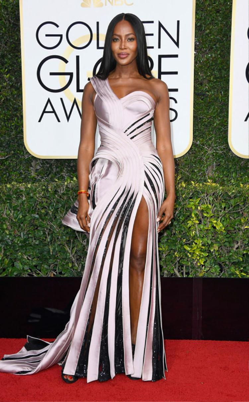 """Nàng """"báo đen"""" Naomi Campbellgợi cảm với một thiết kế cut-out xếp pli của nhà mốt Versace. Dường như điểm nhấn hình ảnh khi cô xuất hiện đến từ mái tóc 2 mái """"trứ danh"""" của mình."""