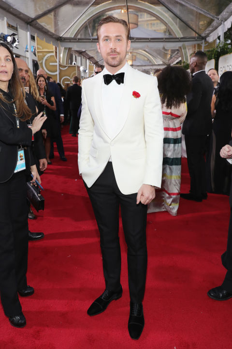 """Chàng diễn viên điển trai trong La La Land không hề thua kém bất kì mỹ nhân nào khi xuất hiện với bộ suit lịch lãm hòa phối giữa hai gam màu đen và trắng cổ điển. Điểm nhấn độc đáo trên toàn set đồ của """"soái ca"""" đến từ mẫu hoa cài áo sắc đỏ nổi bật."""