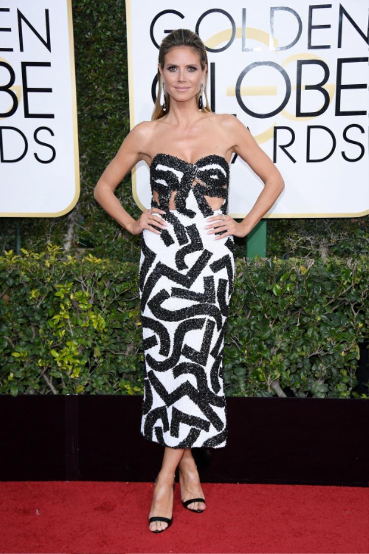 Siêu mẫu Heidi Klum xuất hiện như một quý cô nóng bỏng trong một thiết kế của nhà mốt J.Mendel. Điểm nhấn nhá trên trang phục người đẹp đến từ những đường line đen sequin nổi bật. Không những thế cô nàng còn phối kết đôi hoa tai vô cùng ăn nhập trên tổng thể set đồ.