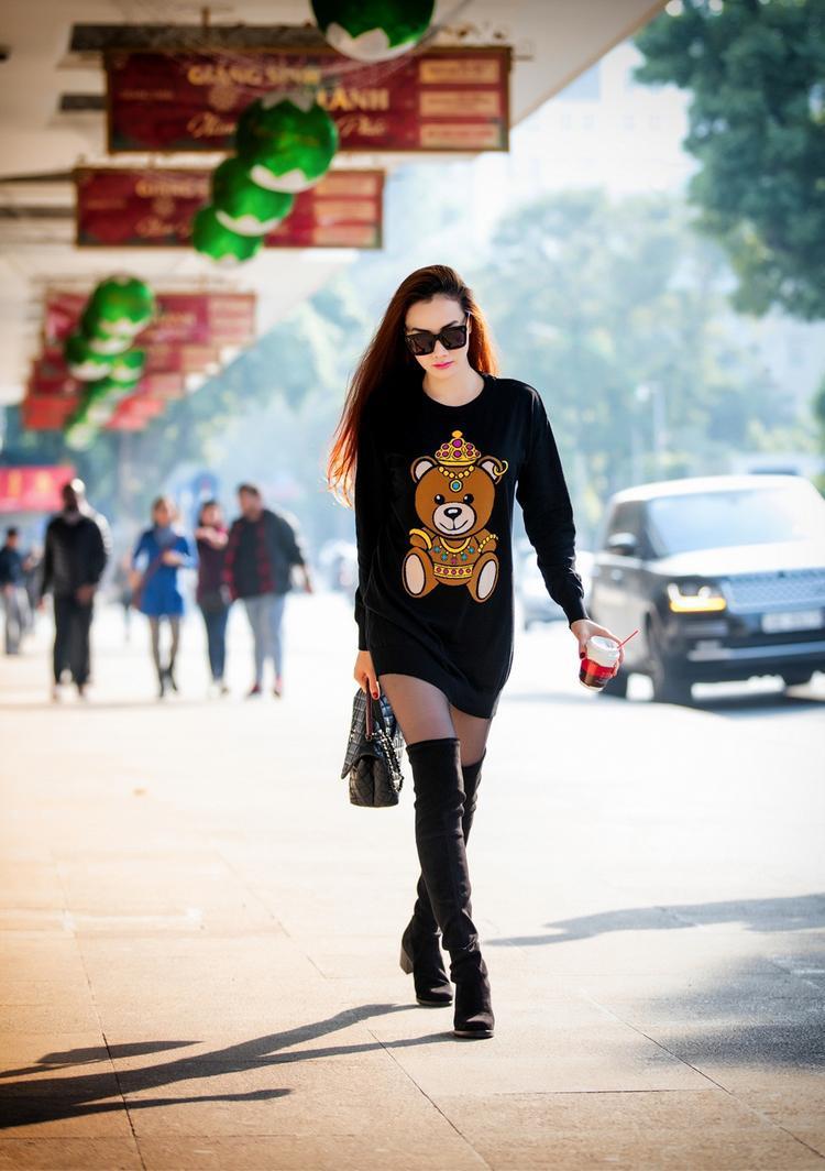 """Áo thun hiệu Moschino với họa tiết gấu đáng yêu kết hợp cùng boot dài trên gối là """"vũ khí"""" lợi hại để Trang Nhung khoe đôi chân thon dài trên phố."""