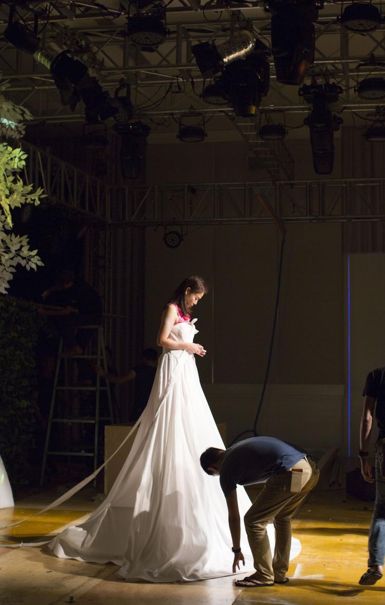 Thu Minh mặc chiếc váy dài lê thê trên sân khấu dưới ánh đèn tỏa sáng như một nữ thần.