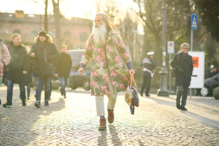 """""""Chàng"""" fashionisto cao tuổi thu hút cánh săn ảnh nhờ vào phong cách thời trang cực độc đáo của mình. Quý ông lựa chọn mẫu áo khoác dáng dài họa tiết camo màu sắc nổi bật hòa phối cùng quần kha ki gam trung tính với điểm nhấn đến từ đôi giày sneaker trẻ trung."""