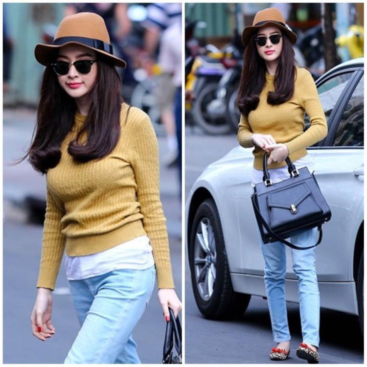 Cũng là mix với jeans nhưng bà mẹ nhí lại kết hợp áo len vặn thừng cùng sơ mi trắng. Sẽ là một set đồ nhàm chán nếu như Angeala Phương Trinh không lựa chọn chiếc mũ rộng vành và cặp kính mắt sành điệu. Chiếc túi hiệu giúp set đồ tăng vài phần sang chảnh.