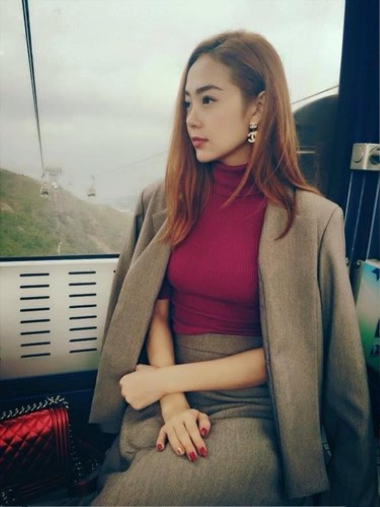 Không vintage, Minh Hằng chuyển hẳn sang hình tượng quý cô với áo len đỏ trơn và khoác blazer hờ hững, đầy sang chảnh.