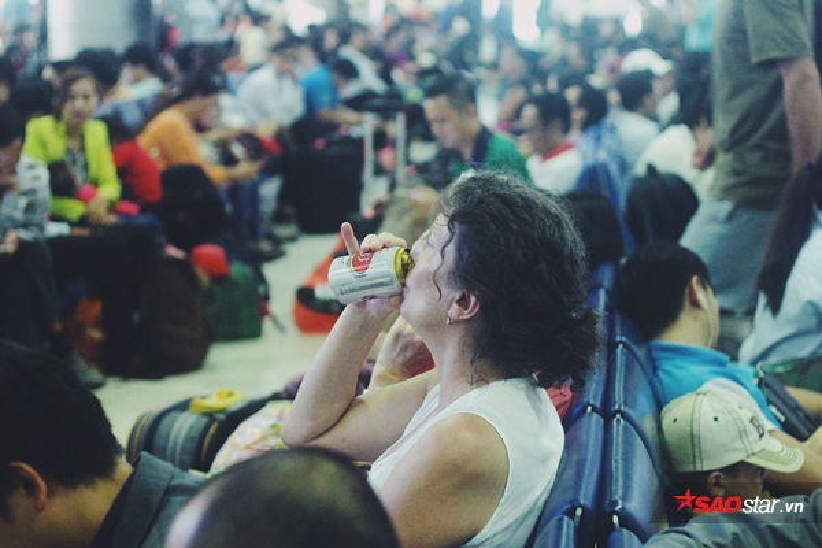 Vì quá mệt mỏi cho nên người phụ nữ ngoại quốc này phải uống bia để giải khát.