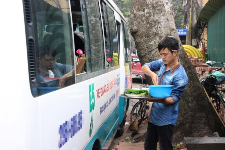 Nhân viên phục vụ khách ăn bún chả qua cửa kính ô tô. Ảnh Dân trí