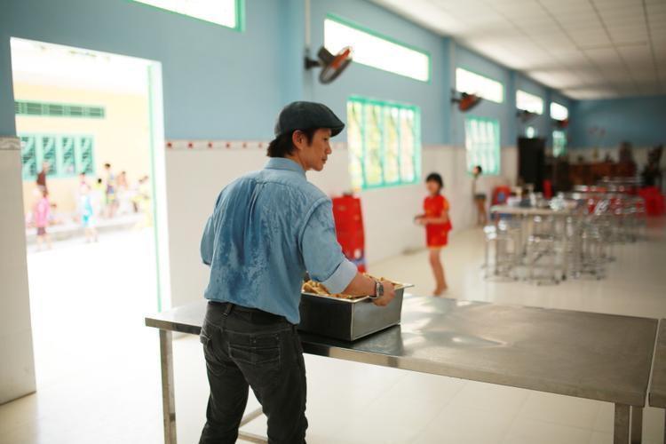 Dustin Nguyễn ướt đẫm mồ hôi trong quá trình chuẩn bị cơm cho các trẻ em.